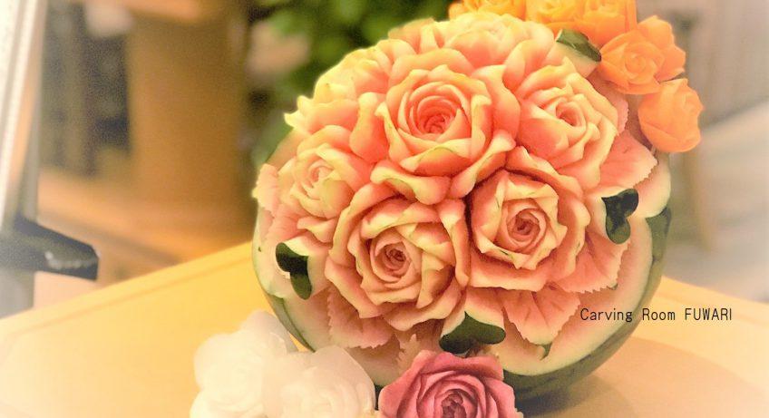 ウェルカムコーナーに飾るオーダーオーダーフルーツカービングのスイカ 周りも薔薇はベジタブルカービング